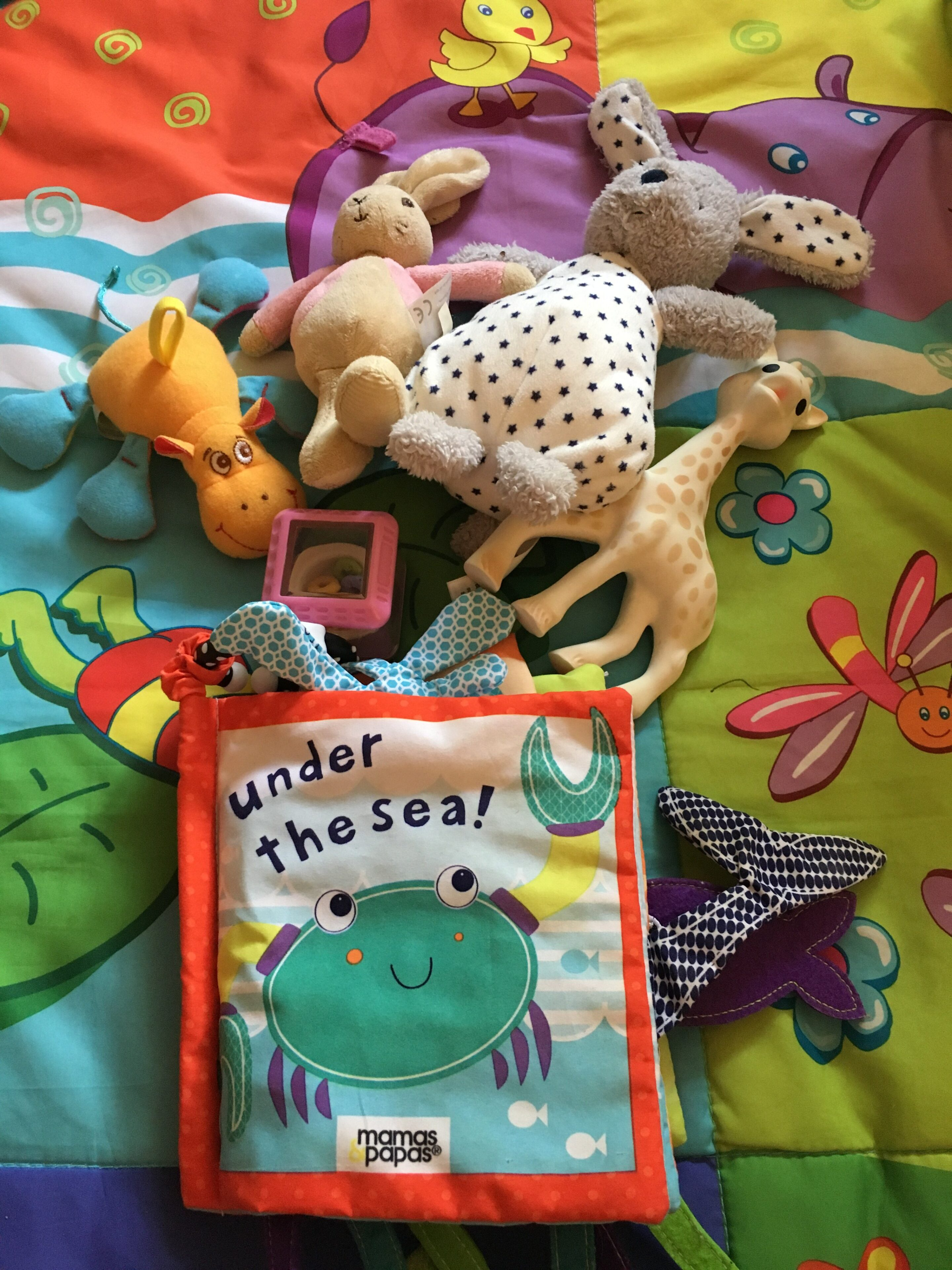 Toys for a baby including Sophie the Giraffe and rattles