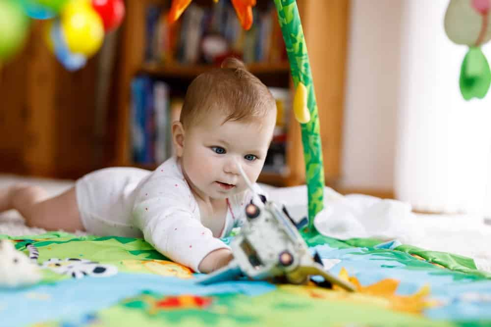Baby playing during tummy time - fine motor skills development activity for babies