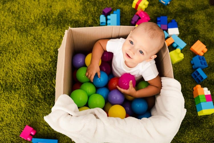 Baby exploring in a box of toys - fine motor development activity